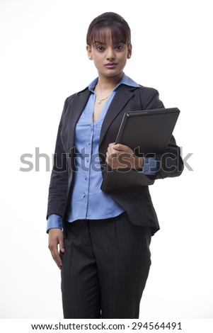 Portrait of confident young businesswoman holding laptop over white background