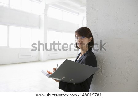 Portrait of confident young businesswoman leaning against wall with paperwork in empty warehouse