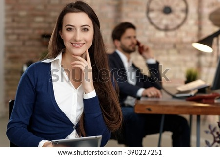 Portrait of confident young businesswoman sitting in office, smiling, looking at camera. - stock photo