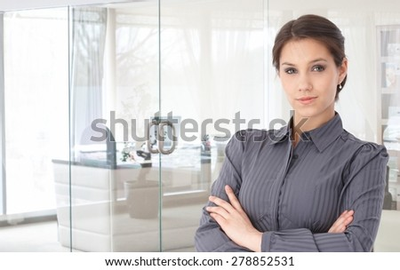 Portrait of confident young businesswoman standing arms crossed at bright office. - stock photo