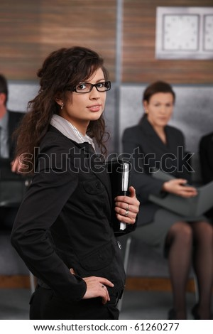 Portrait of confident young businesswoman standing in office with hand on her hip, looking back.? - stock photo