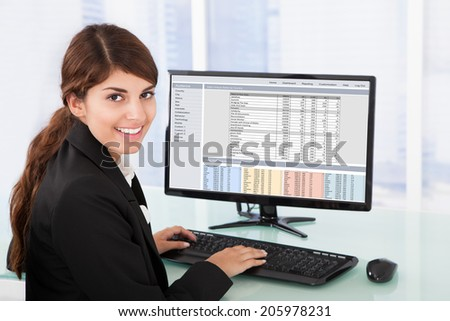 Portrait of confident young businesswoman using computer at desk in office - stock photo