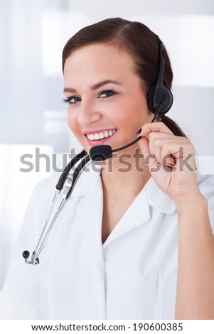 Portrait of confident young female doctor wearing headset in hospital - stock photo
