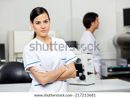 Portrait of confident young female scientist with colleague in background at laboratory - stock photo