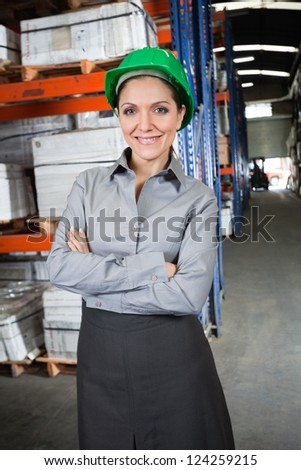 Portrait of confident young female supervisor with arms crossed standing at warehouse