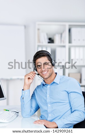 Portrait of confident young male customer service executive communicating on headset at desk in office - stock photo