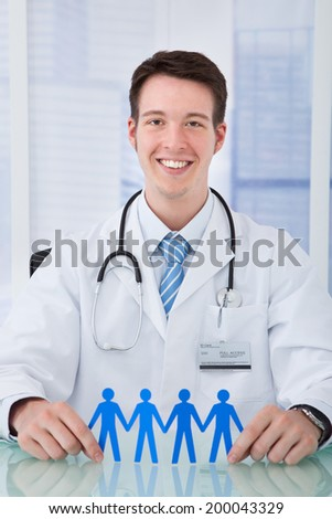 Portrait of confident young male doctor holding blue paper people chain at desk in clinic - stock photo