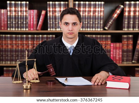 Portrait of confident young male judge striking the gavel at table against bookshelf