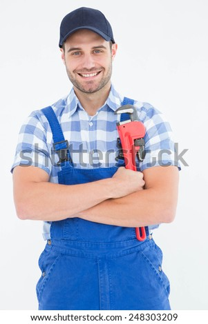 Portrait of confident young male repairman holding adjustable spanner on white background - stock photo