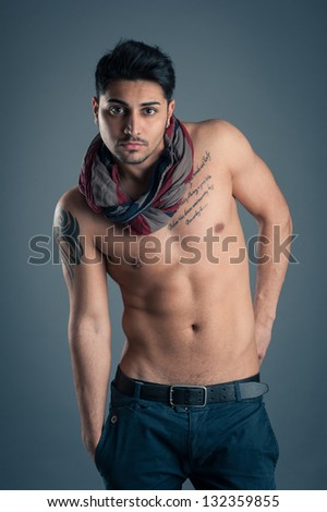Portrait of confident young man shirtless against dark background. - stock photo