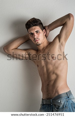 Portrait of confident young man shirtless against white wall.