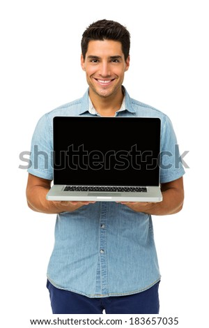 Portrait of confident young man showing laptop against white background. Vertical shot. - stock photo