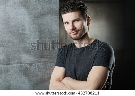 Portrait of confident young man, smiling, looking at camera, standing arms crossed. - stock photo