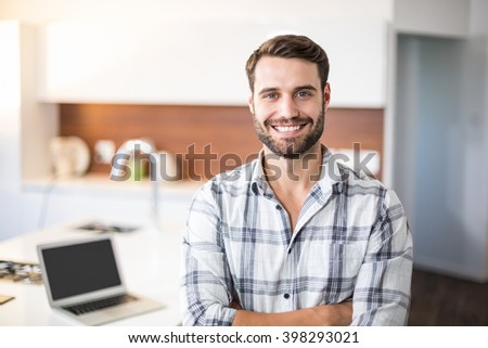 Portrait of confident young man standing by kitchen counter - stock photo