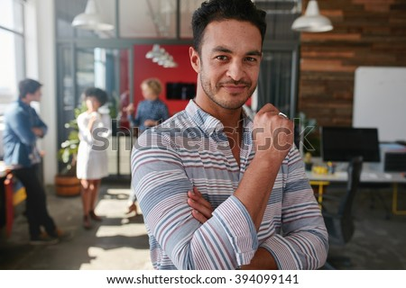Portrait of confident young man standing in his office. Caucasian man at his work place with colleagues talking in background. - stock photo