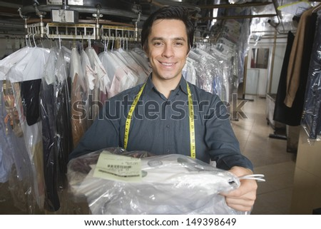 Portrait of confident young owner giving dry cleaned clothes in laundry - stock photo