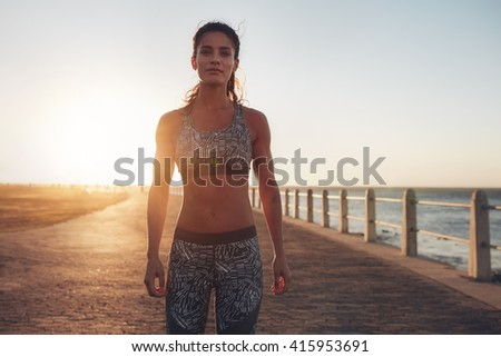 Portrait of confident young sportswoman standing on a seaside road at sunset. Female wearing sportswear looking at camera. - stock photo