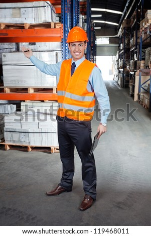 Portrait of confident young supervisor showing stock on shelves at warehouse - stock photo