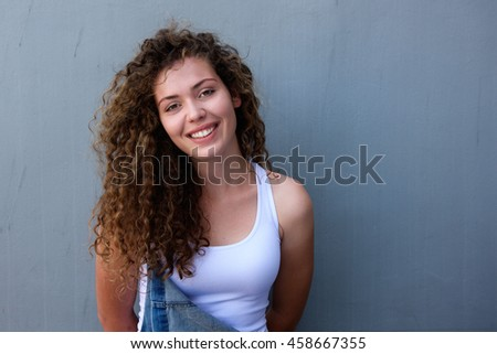 Portrait of confident young teen girl smiling in overalls - stock photo