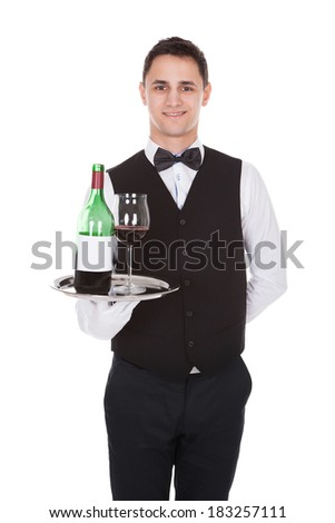 Portrait of confident young waiter holding tray with glass of red wine and bottle against white background - stock photo