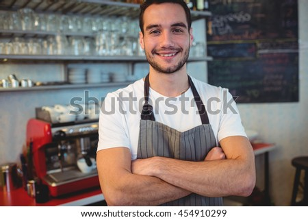 Portrait of confident young waiter with arms crossed at cafe