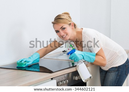 Portrait of confident young woman cleaning induction stove at home - stock photo