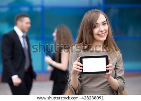 Portrait of confident young woman holding tablet with blank white copy space screen and looking at camera with happy facial expression outdoors. Successful beautiful woman showing empty monitor - stock photo