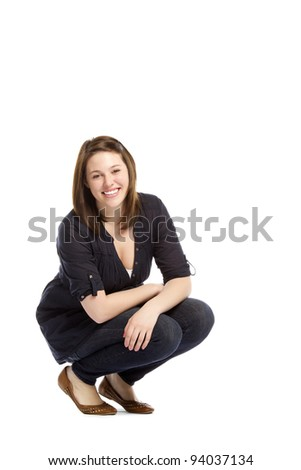 Portrait of confident young woman sitting on white background - Studio shot