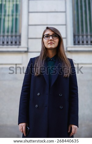 Portrait of confident young woman wearing winter clothing standing in the city - stock photo