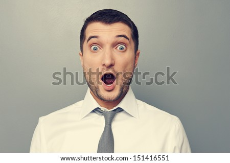 portrait of confused businessman wit open mouth over grey background - stock photo
