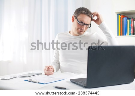 Portrait of confused young man using laptop - stock photo