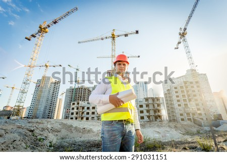 Portrait of construction inspector posing with blueprints on building site - stock photo