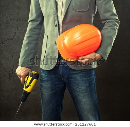 Portrait of construction master holding yellow helmet and drill in hands. - stock photo