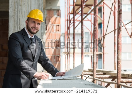 Portrait Of Construction Master With Yellow Helmet And Blueprint In Hands - stock photo