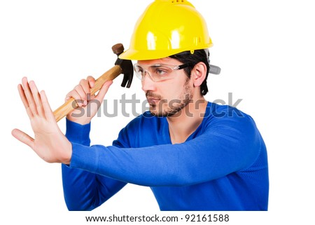 portrait of construction worker holding hammer and wearing yellow safety helmet.