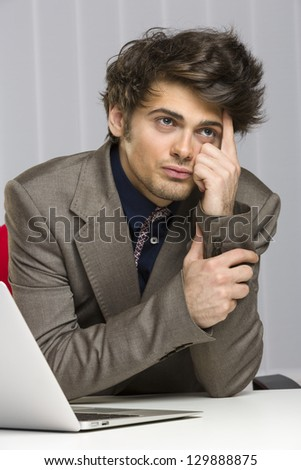 Portrait of contemplative handsome young business guy sitting at desk in his office. - stock photo