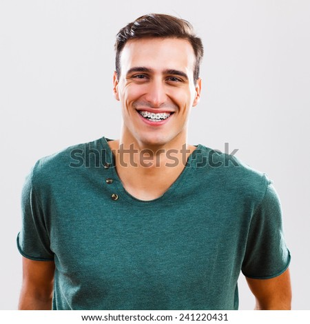 Portrait of content  young man with braces,Young man with braces - stock photo