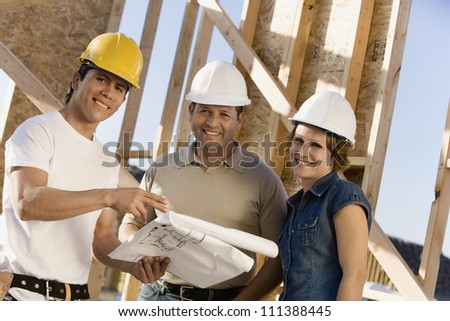 Portrait of contractors with blueprint discussing at construction site - stock photo
