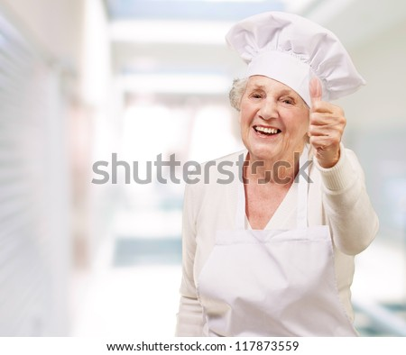 portrait of cook senior woman doing good gesture at restaurant - stock photo