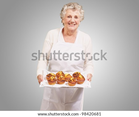 portrait of cook senior woman holding a chocolate muffins tray over a grey background - stock photo