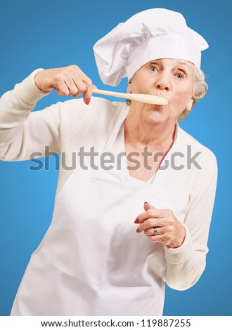 portrait of cook senior woman with wooden spoon on mouth over blue - stock photo