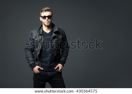 Portrait of cool looking handsome young man in casual wear standing against dark background. - stock photo