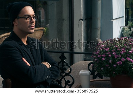 Portrait of cool stylish handsome lonely hipster guy wearing all black in hat and glasses sitting in cafe drinking coffee during sunny morning