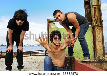Portrait of cool team of young friends posing outdoors - stock photo