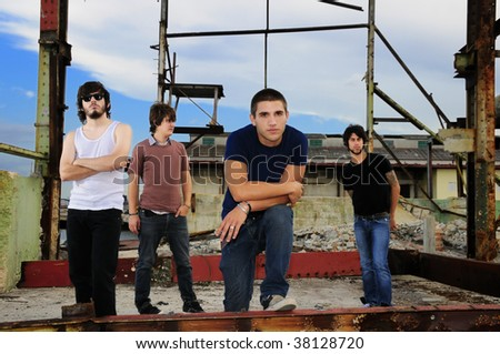 Portrait of cool team of young male friends posing outdoors - stock photo
