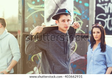 Portrait of cool  teenage boy with a skateboard on his shoulder - stock photo