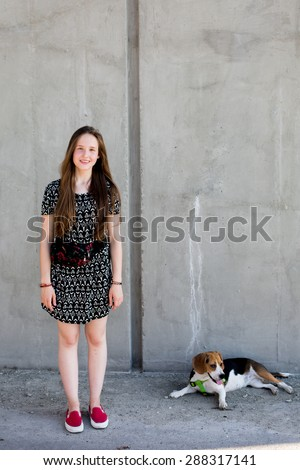 portrait of cool young and beautiful caucasian blonde teenager hipster girl with long gorgeous hair is posing smiling and having fun with her beagle puppy dog - stock photo