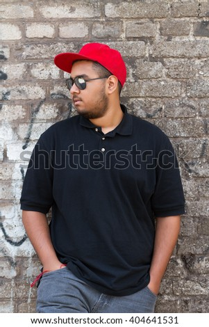 Portrait of cool young black boy in red baseball cap and sunglasses at grey brick wall with graffiti - stock photo