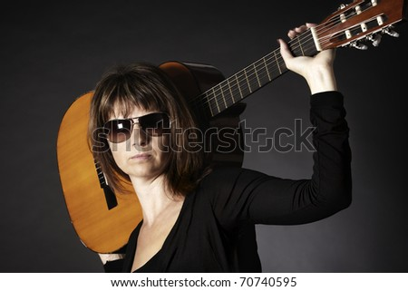 Portrait of cool young woman in black posing with guitar on shoulders, isolated on black background. - stock photo