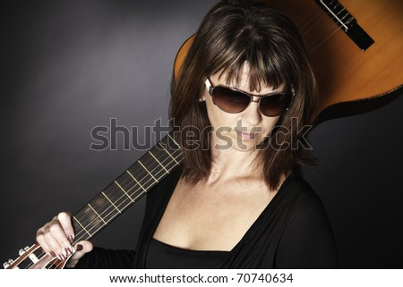 Portrait of cool young woman in black posing with guitar on shoulders looking down, isolated on black background. - stock photo